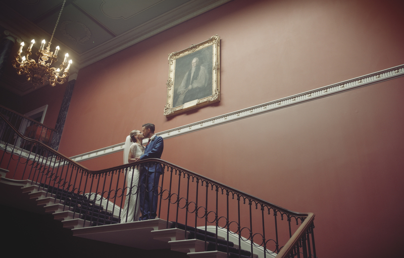 Bride and Groom Kiss on the stairs at Rise Hall