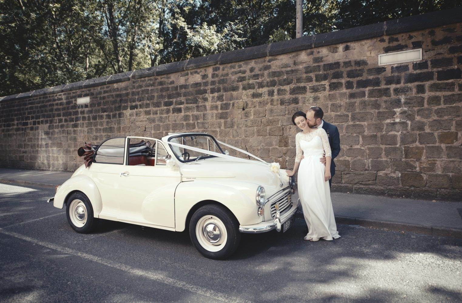 A bride and groom with their wedding car outside the The Faversham Leeds
